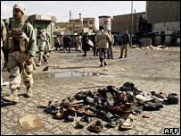An Iraqi soldier stands beside the shoes of dead and wounded from Friday's Ghazil market blast, 1 February 2008