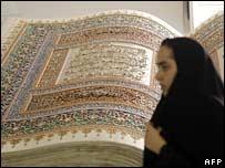An Iranian woman walks past a large Koran