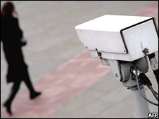 A woman watched by a CCTV camera