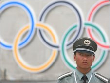 A Chinese security guard stands in front of the Olympic rings on Beijin's Tiananmen Square