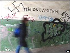 """A woman walks past graffiti reading """"We love you!"""" with a swastika mocking migrants"""