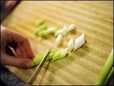Chopping spring onions on a board