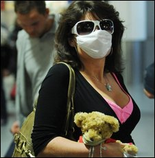 An airline passenger wearing a protective face mask arrives at Gatwick Airport, south of London, on a flight from Cancun in Mexico, 30 April.