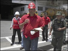 Venezuela's Deputy Food Minister Rafael Coronado leads a group of officials and soldiers towards the pasta plant in Catia la Mar on the outskirts of Caracas