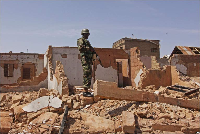 A Nigerian soldier stands on the rubble of a destroyed building