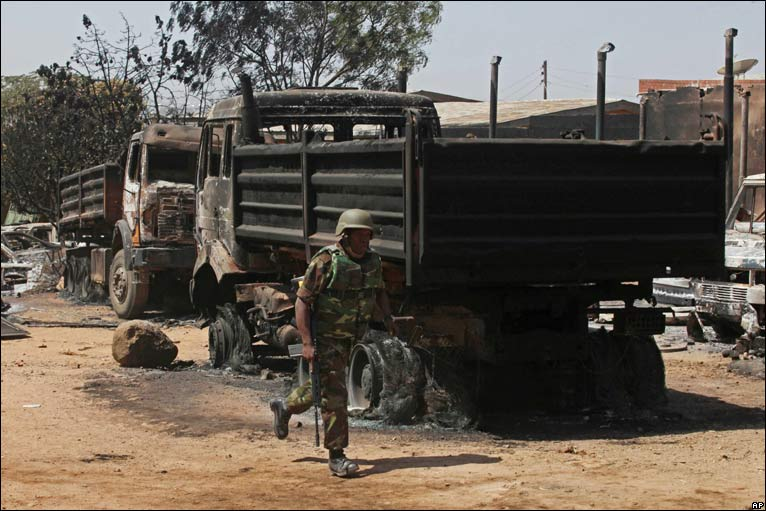 Soldier runs past a burnt-out truck in Jos
